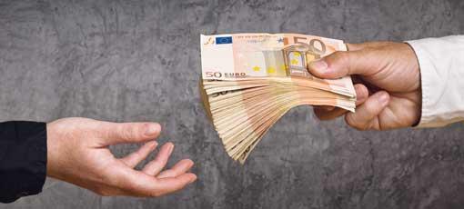 Einem Studenten wird ein großer Geldbündel zur Finanzierung überreicht