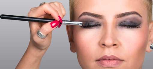 Geprüfte Kosmetikerin schminkt Modell