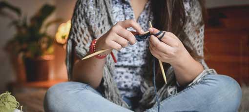 Eine junge Studentin lernt modernes Stricken