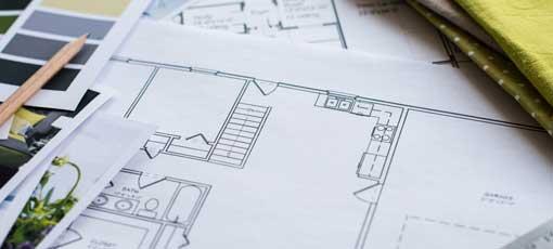 Innendesigner gleicht Stoffmuster und Farbpaletten mit dem Bauplan des Hauses ab